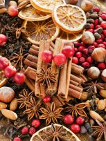 Christmas spices, fruits, nuts and berries on the wooden background. Shallow dof.